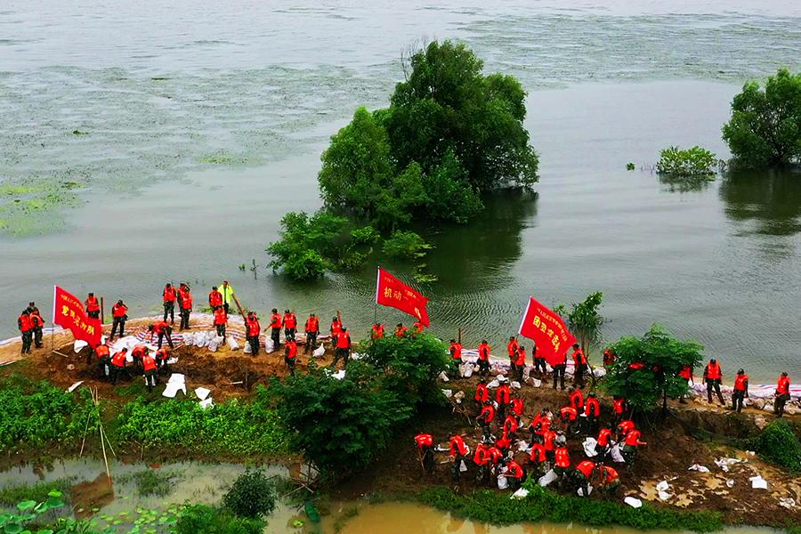 踩泥濘戰高溫,武警官兵肩扛車推加固堤壩